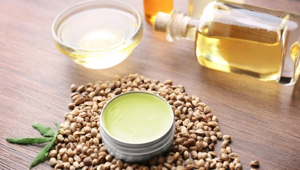 Composition with hemp lotion, oil and seeds on wooden background