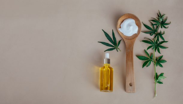 Glass bottle and dropper CBD OIL, THC tincture and cannabis leafs on pastel background. Laboratory Production of cosmetics with CBD oil.